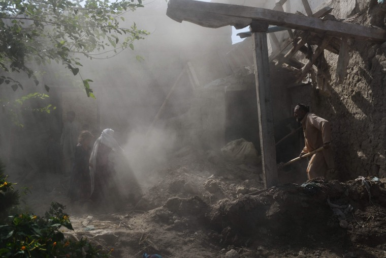 Image: Residents clear rubble from their homes