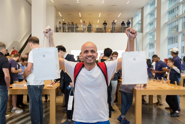 Image: A man stands with two bags of purchases at the iPhone 8 Launch at the 5th Avenue Apple Store