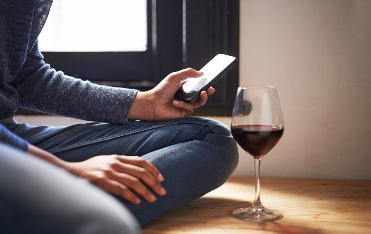 Image: A woman sends a text message with a glass of wine beside her