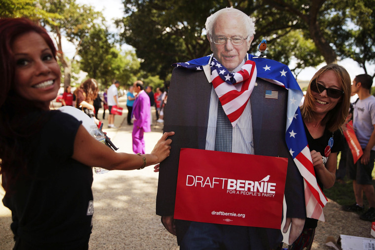 Image: Supporters of Sen. Bernie Sanders hold a cardboard cutout of the senator during a rally