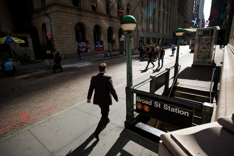 Image: A pedestrian walks along Wall Street