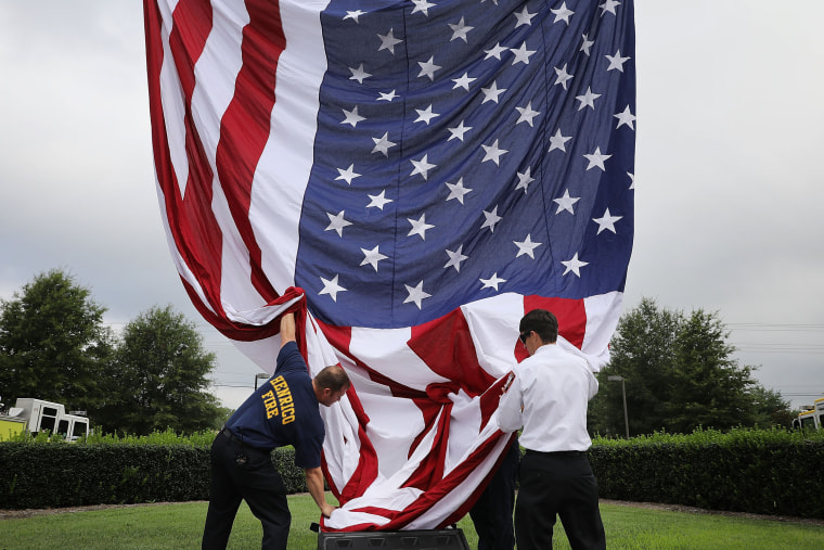 Image: Firefighters raise a U.S. flag ahead of a funeral