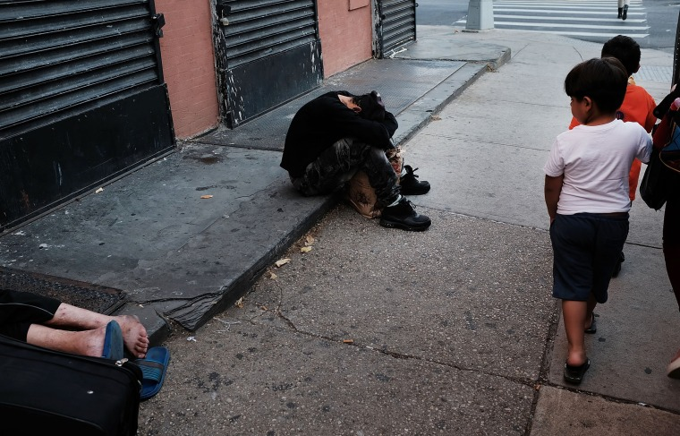Image: Children walk by drug users passed out along a street in a South Bronx neighborhood