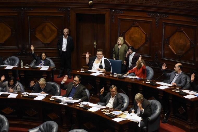 Image: Sen. Michelle Suarez, center back, in white scarf, votes during a Senate session in Montevideo