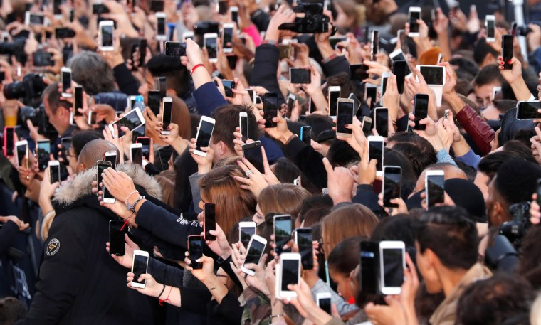 Image: People use their smartphone to take photos