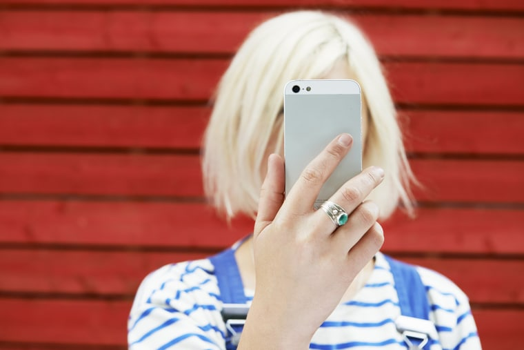 Image: woman holding up mobile for selfie