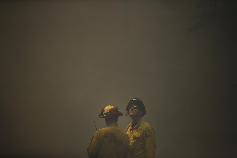 Image: Firefighters watch as think smoke from a wildfire fills the air near Calistoga, California