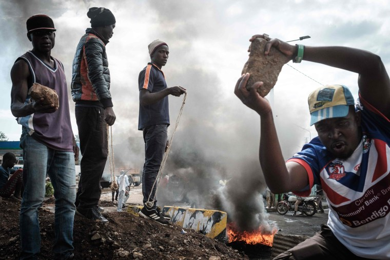 Image: Opposition supporters hold up bricks as they block streets and burn tires during a protest in Kisumu