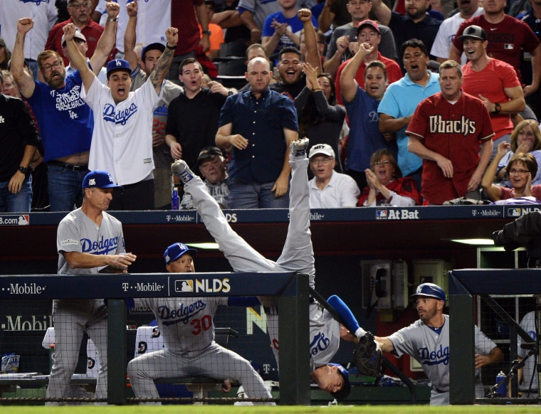 Image: Los Angeles Dodgers first baseman Cody Bellinger falls over the railing as he catches a fly ball