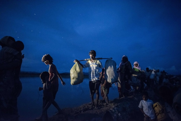Image: Rohingya refugees walk after crossing the Naf river from Myanmar into Bangladesh