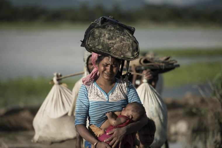 Image: A Rohingya refugee cries as she holds a baby after crossing the Naf river from Myanmar into Bangladesh