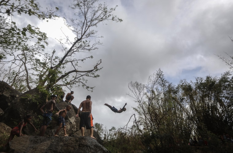Image: A man dives into the Espiritu Santo river, in a hurricane-damaged section of forest, in Palmer, Puerto Rico