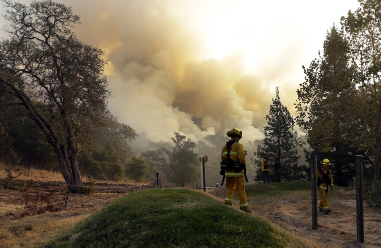 Image: Firefighters walk along a containment line