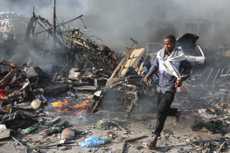 Image: A man runs from the massive explosion in front of Safari Hotel in Mogadishu, Somalia.
