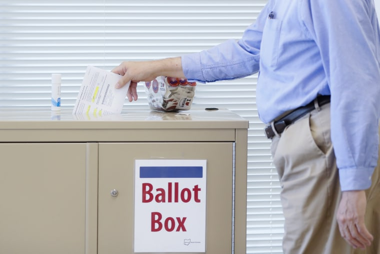 A voter casts a ballot on the first day of early voting at the Hamilton County Board of Elections, Wednesday, Oct. 11, 2017, in Cincinnati. (AP Photo/John Minchillo)