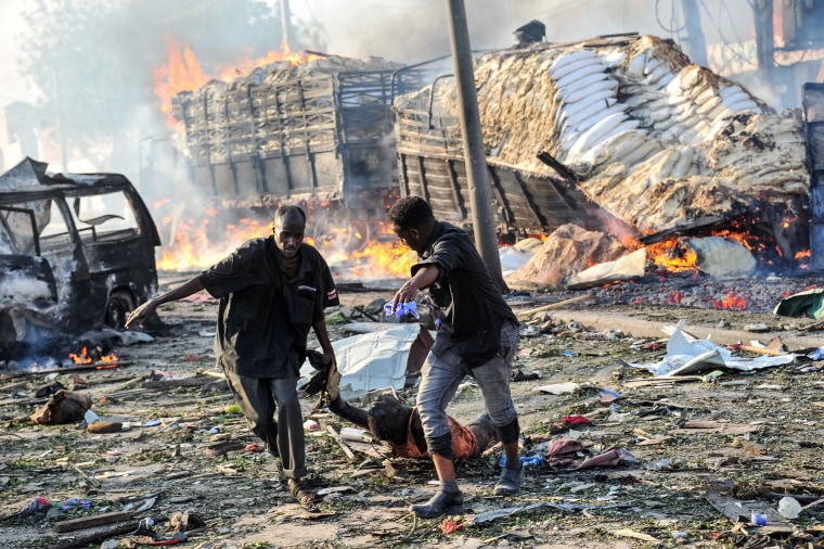 Image: Two men carry the body of a victim following the explosion of a truck bomb
