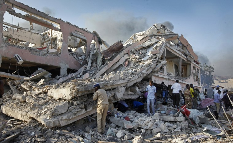 Image: Somalis gather and search for survivors by destroyed buildings at the scene of a blast