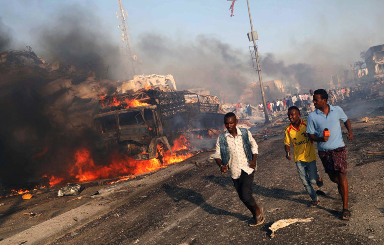 Image: Civilians evacuate from the scene of explosion in Mogadishu