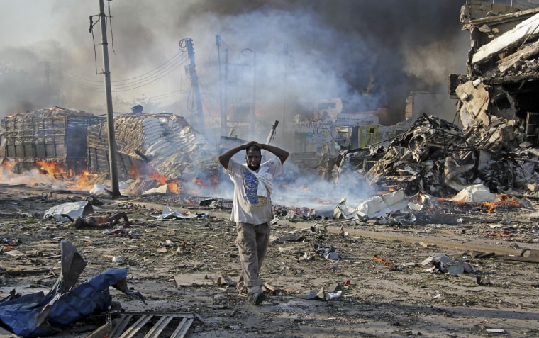 Image: A Somali gestures as he walks past a dead body, left, and destroyed buildings at the scene of a blast