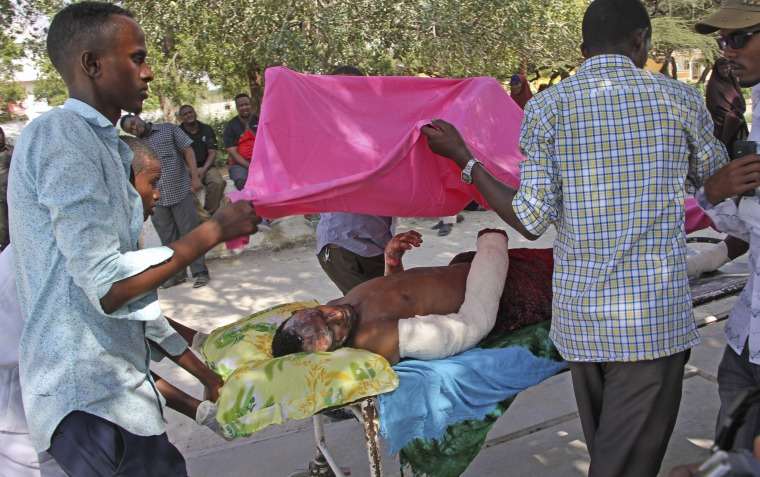 Image: Somalis help a wounded civilian at Medina hospital in Mogadishu