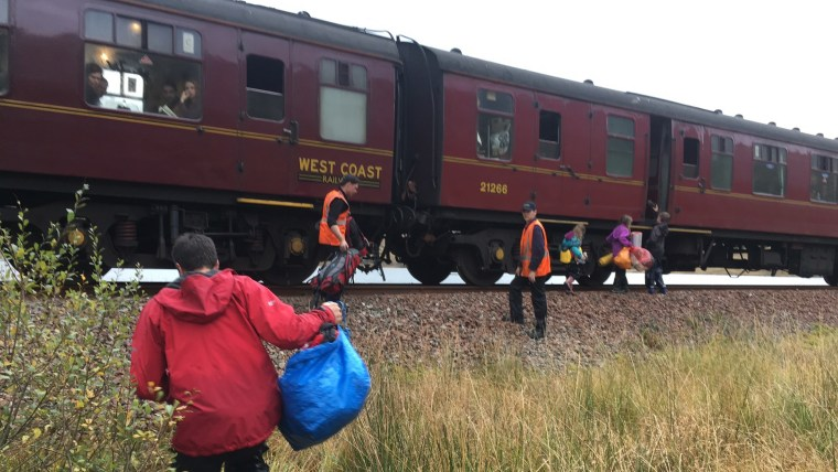 In this photo taken on Friday, Oct. 13, 2017, children run towards a train near Loch Eilt in  the Scottish Highlands. As if by magic, the Hogwarts Express has come to the rescue of a stranded family in Scotland.