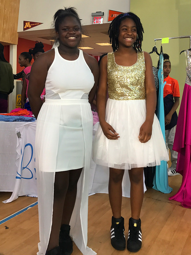 Students in Atlanta smile in their new dresses.
