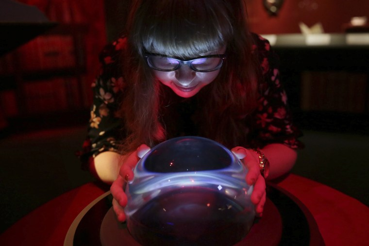 "A member of British Library staff poses with a crystal ball for a picture at the ""Harry Potter - A History of Magic"" exhibition at the British Library, in London, Wednesday Oct. 18, 2017."