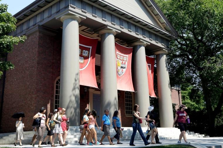 Image: People tour the campus of Harvard University in Cambridge, Massachusetts