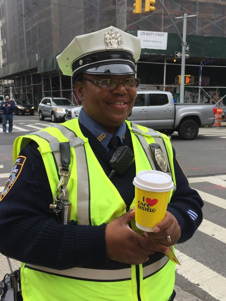 NYPD police officer with cup of Bustelo coffee outside of Pop Up Bustelo store in New York City.