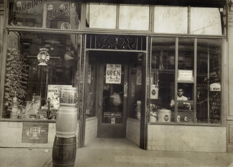 "Jose Mora (in the small window), from Aragon Spain, owned and ran Fifth Avenue Hardware, which was directly across the street from Gregorio Bustelo's first storefront, on Fifth Avenue, in the heart of the neighborhood that was becoming known in the 1930s as ""El Barrio"" or Spanish Harlem."
