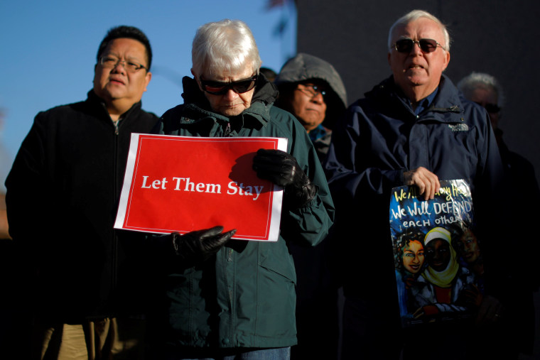 "Image: Demonstrators hold an ""Interfaith Prayer Vigil for Immigrant Justice"" outside the federal building in Manchester"