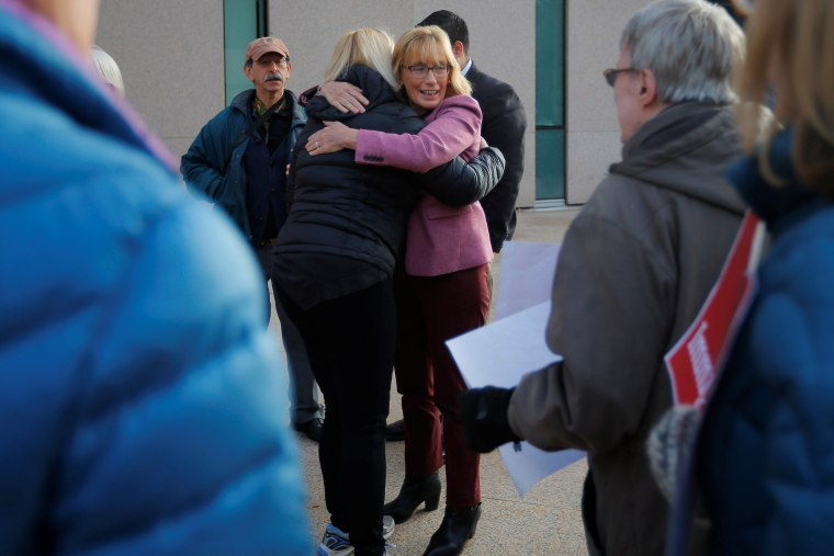 """Image: U.S. Senator Hassan hugs demonstrators holding an """"Interfaith Prayer Vigil for Immigrant Justice"""" outside the federal building in Manchester"""