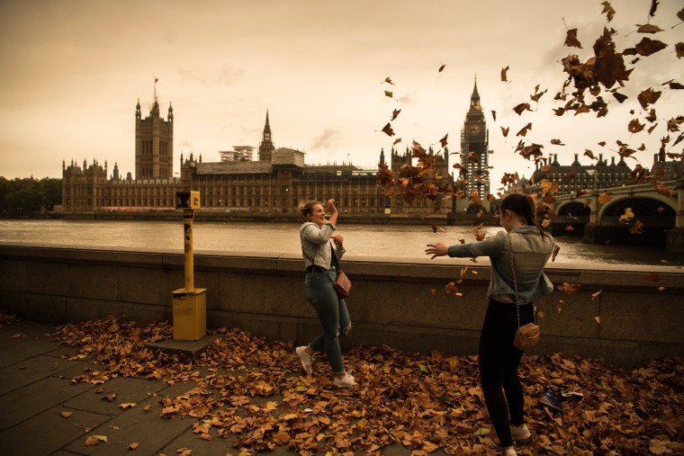 Image: Girls throw leaves opposite the Houses of Parliament during a reddish sky caused by remnants of Hurricane Ophelia