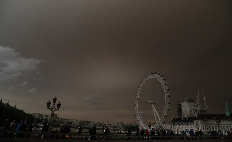 Image: The sky over the London Eye is bathed in a dull orange sky in London