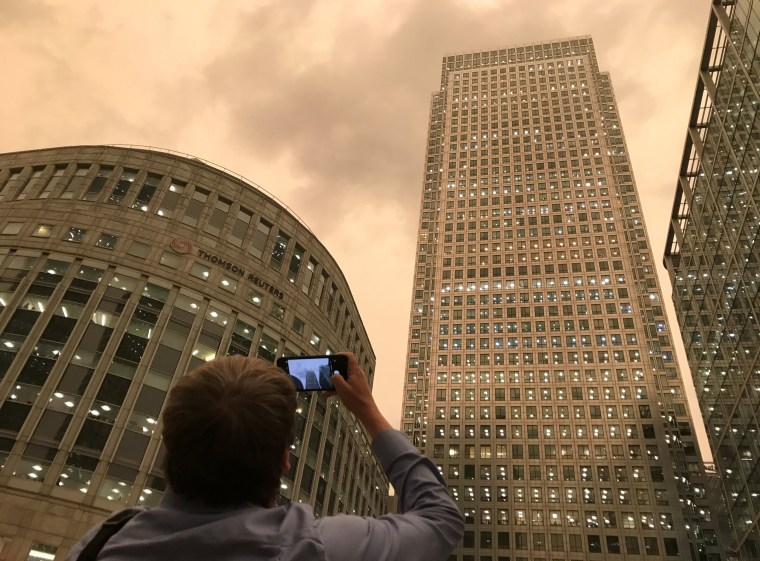 Image: The sky turns dark during mid-afternoon in the financial district of Canary Wharf