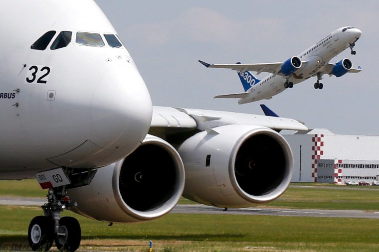 Image: A Bombardier CS300 aicraft takes as an Airbus A380 waits on the taxiway in this 2015 file photo.