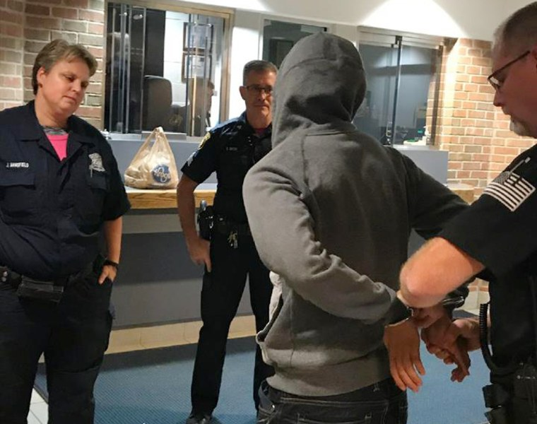 Image: Michael Zaydek, known on social media as Champagne Torino is handcuffed at the Redford Township Police Department