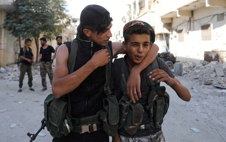 Image: Teen fighters of Syrian Democratic Forces joke each other in Raqqa