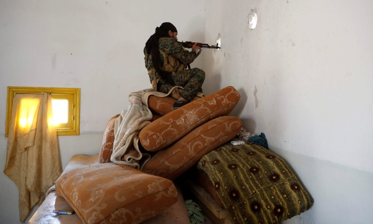 Image: A fighter of Syrian Democratic Forces takes up a position inside a house in Raqqa