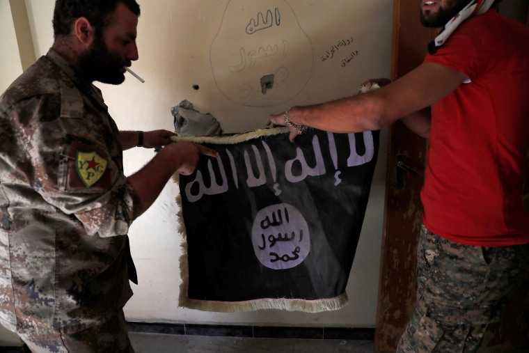 Image: Members of Syrian Democratic Forces hold a flag of the Islamic State militants recovered at a building next to the stadium in Raqqa