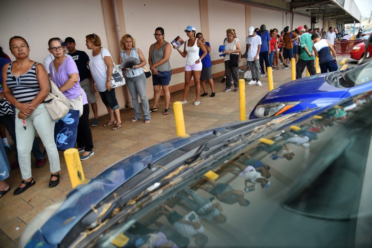 Image: People wait in a line to buy food at a supermarket in Humacao