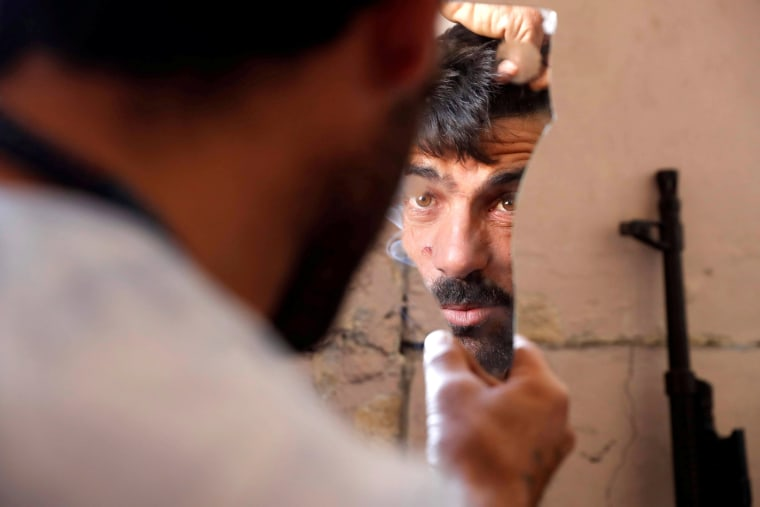 Image: A fighter of Syrian Democratic Forces fixes his hair using a broken mirror at the frontline in Raqqa