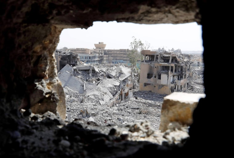 Image: The National Hospital, last stronghold of the Islamic State militants, is pictured from a hole at the positions of the Syrian Democratic Forces at the frontline in Raqqa