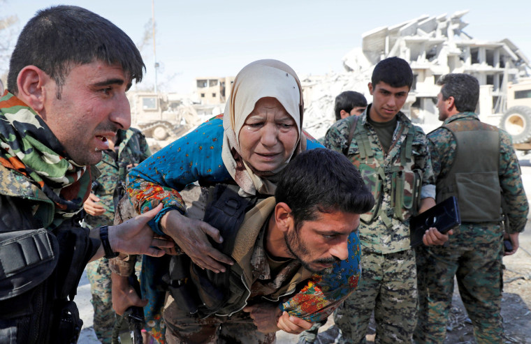 Image: Fighters of Syrian Democratic Forces evacuate a civilian from the stadium after Raqqa was liberated from the Islamic State militants in Raqqa