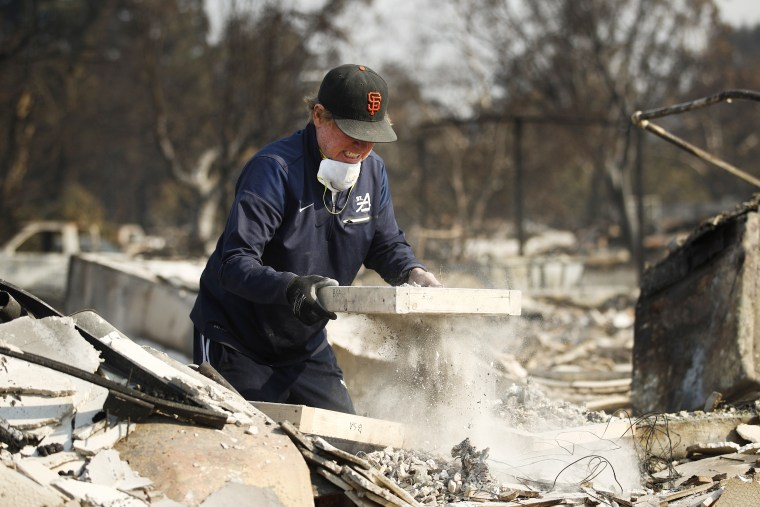 Image: Ed Curzon sifts debris to salvage anything he can from the rubble of his home