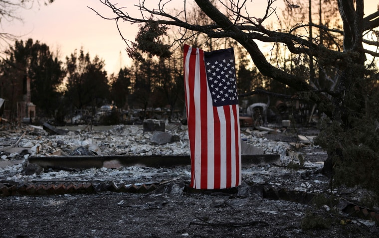 Image: An American flag hangs from a tree in a neighborhood destroyed by wildfire in Santa Rosa, California, U.S.