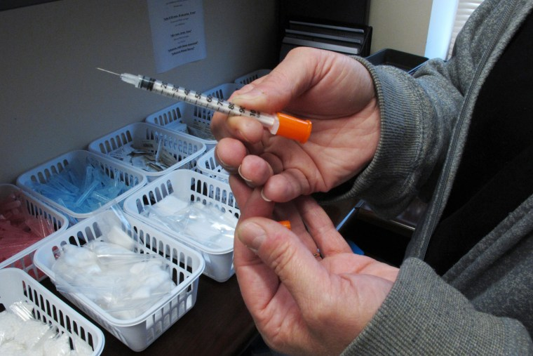Image: A public health nurse holds one of the syringes provided to intravenous drug users