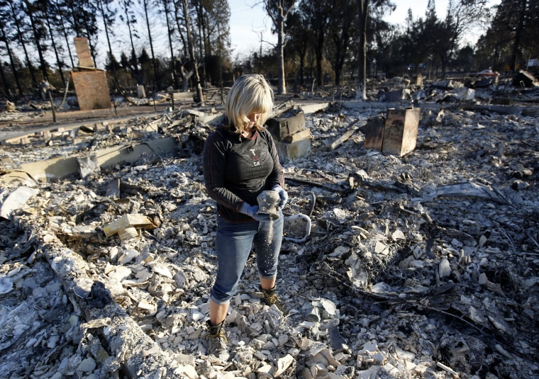 Image: Debbie Wolfe dumps ashes from a pot she found in the burned ruins of her home
