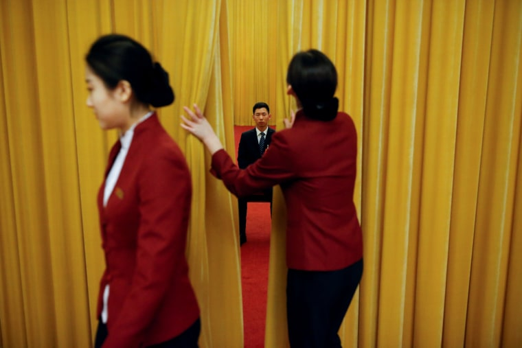 Image: A security officer keeps watch behind a curtain on the second day of the 19th National Congress of the Communist Party of China at the Great Hall of the People in Beijing