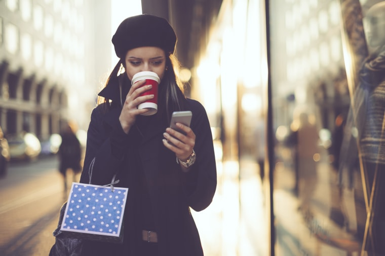 Image: A woman carrying a shopping bag drinks coffee while looking at her mobile phone